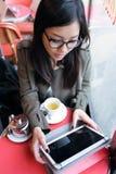 使用她的数字式片剂的美丽的年轻亚裔妇女,当喝咖啡在咖啡店时 免版税库存照片