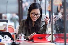 使用她的数字式片剂的美丽的年轻亚裔妇女,当喝咖啡在咖啡店时 库存图片