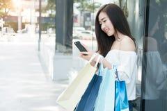 使用她的智能手机和举行购物袋whi的年轻aisin妇女 免版税图库摄影