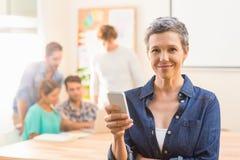使用她的智能手机的偶然女实业家和微笑对照相机 免版税图库摄影