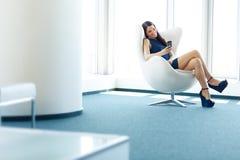 使用她的智能手机的女商人在办公室 事务Peop 免版税库存照片