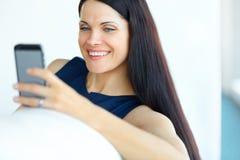 使用她的智能手机的女商人在办公室 库存照片