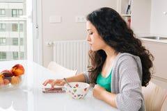 使用她的智能手机的少妇,当早餐时 免版税库存照片