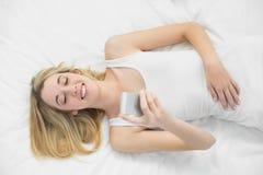 使用她的智能手机的愉快的白肤金发的妇女说谎在她的床上 图库摄影