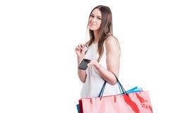 使用她的智能手机的美丽的少妇,当做某一商店时 免版税库存图片