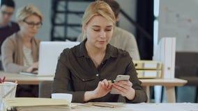 使用她的有微笑的快乐的年轻美丽的妇女智能手机,当坐在她的工作地点时 影视素材