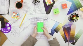 E 使用她的有绿色屏幕的妇女设计师智能手机在桌,卷动新闻,照片里 影视素材