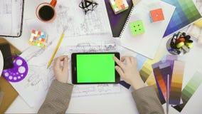 E 使用她的有绿色屏幕的妇女设计师片剂在桌,卷动新闻,照片里 影视素材
