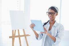 使用她的片剂个人计算机的快乐的可爱的艺术家 库存照片