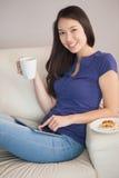使用她的片剂个人计算机的年轻愉快的亚裔妇女和举行杯子c 免版税库存图片
