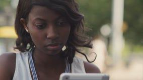 使用她的片剂的非裔美国人的妇女 库存图片