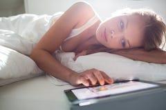 使用她的片剂计算机的俏丽,少妇在床 库存照片