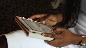 使用她的片剂计算机的非裔美国人的妇女的特写镜头手 股票录像