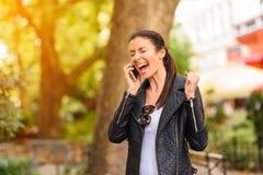 使用她的电话的一个愉快的少妇在一个城市环境 免版税库存图片