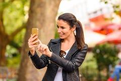 使用她的电话的一个愉快的少妇在一个城市环境 免版税库存照片