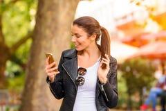 使用她的电话的一个愉快的少妇在一个城市环境 库存照片