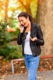 使用她的电话的一个愉快的少妇在一个城市环境 图库摄影
