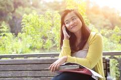 使用她的电话的女性大学生,坐长木凳在公园 免版税库存照片