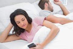 使用她的电话的妇女,当她的丈夫睡觉时 库存图片
