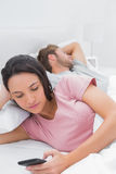 使用她的电话的妇女,当她的伙伴睡觉时 免版税库存图片