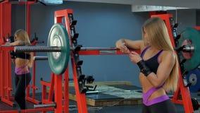 使用她的电话的年轻运动妇女在健身房 库存图片