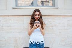 使用她的电话的年轻人微笑的美丽的女孩户外 库存照片