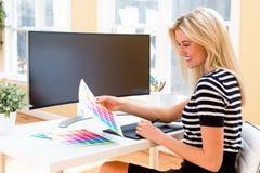 使用她的笔片剂设备的图表设计师 免版税库存图片
