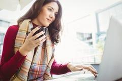 使用她的膝上型计算机的妇女和喝咖啡 库存图片