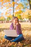 使用她的膝上型计算机的少妇户外在秋天 图库摄影