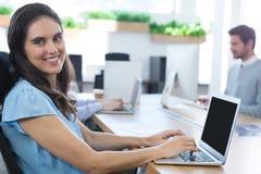 使用她的膝上型计算机的微笑的女性执行委员在办公室 图库摄影