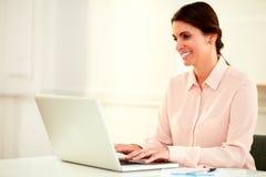 使用她的膝上型计算机的美丽的20s女实业家 免版税库存照片