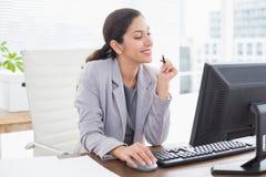使用她的计算机的微笑的女实业家 免版税库存图片