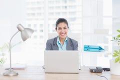使用她的计算机的微笑的女实业家 免版税库存照片