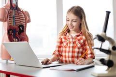 使用她的计算机的甜聪明的女孩为数据分析 库存图片