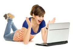 使用妇女年轻人惊奇的膝上型计算机 免版税图库摄影