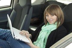 使用妇女年轻人的汽车膝上型计算机 免版税库存照片