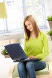使用妇女年轻人的绿色家庭膝上型计&# 库存照片