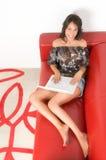 使用妇女年轻人的膝上型计算机位于的沙发 免版税库存图片