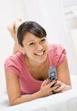 使用妇女年轻人的celular电话纵向 库存照片