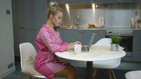 使用妇女的厨房膝上型计算机 股票录像
