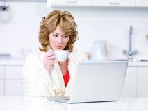 使用妇女的咖啡饮用的膝上型计算机 免版税库存照片