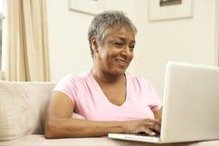 使用妇女的家庭膝上型计算机前辈 库存图片