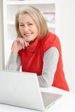 使用妇女的家庭膝上型计算机前辈 免版税库存照片