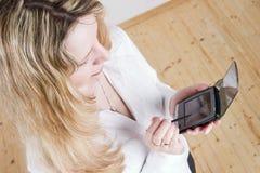 使用妇女的白肤金发的pda 库存图片