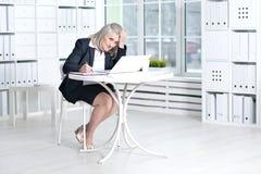 使用妇女的膝上型计算机前辈 免版税库存图片