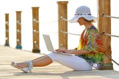 使用妇女的膝上型计算机室外夏天 免版税库存照片