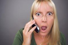 使用妇女震惊的白肤金发的移动电话 库存图片