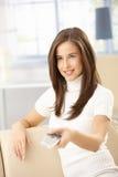使用妇女,控制愉快的遥控 免版税图库摄影