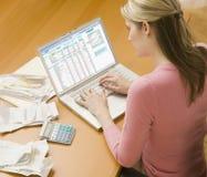 使用妇女,提供经费给膝上型计算机 免版税库存图片