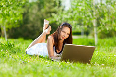 使用妇女年轻人的膝上型计算机公园 免版税库存照片